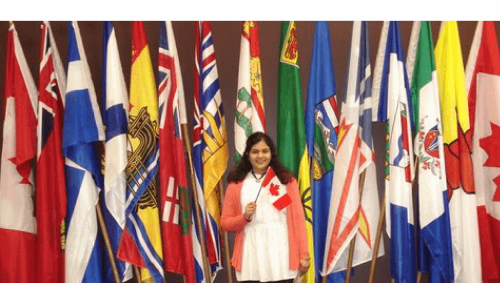 Manveetha holding a Canadian flag with flags from different countries in the background