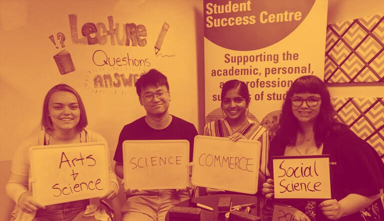 Three students holding signs with their faculty