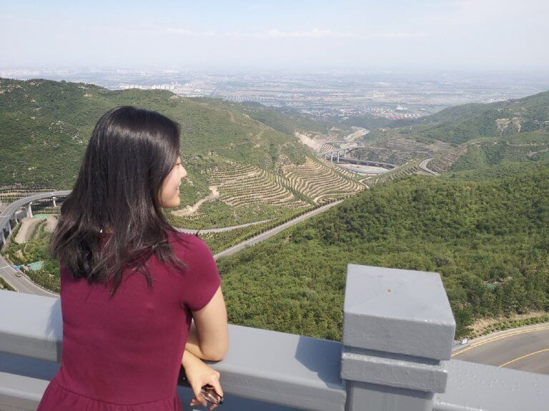 Amy overlooking a green landscape in China