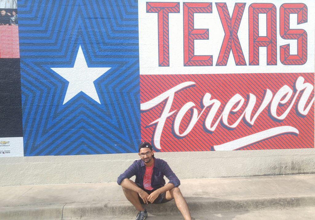 Milan sitting with a Texas Forever sign in the background