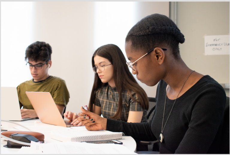 Three students working at a table