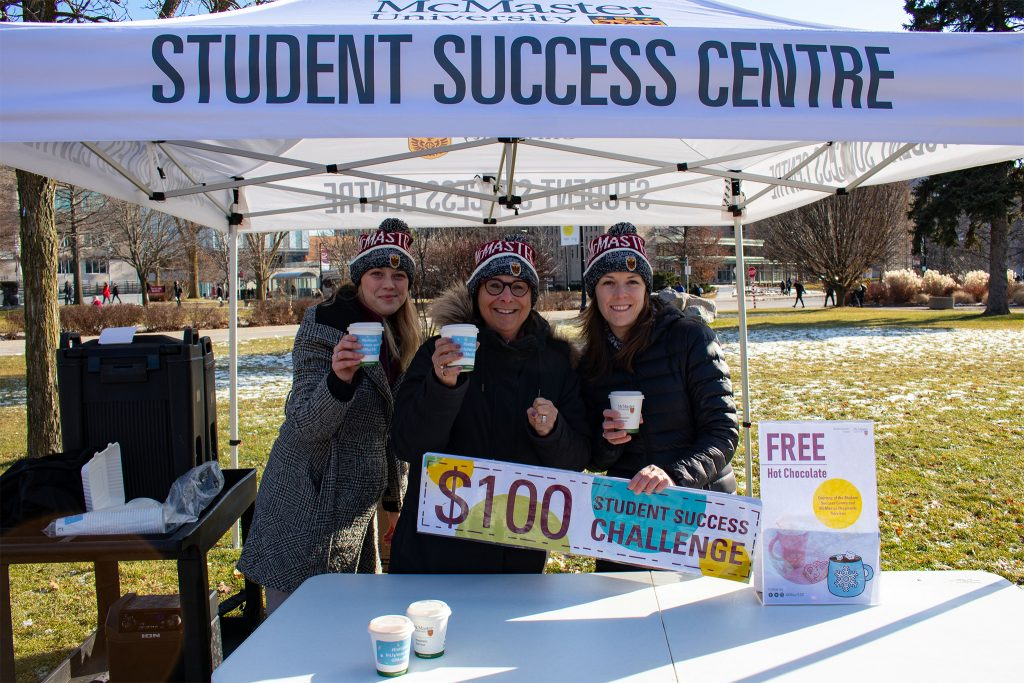 Three Student Success staff holding coffees under a tent that says Student Success Centre. They are also holding a sign that says $100.