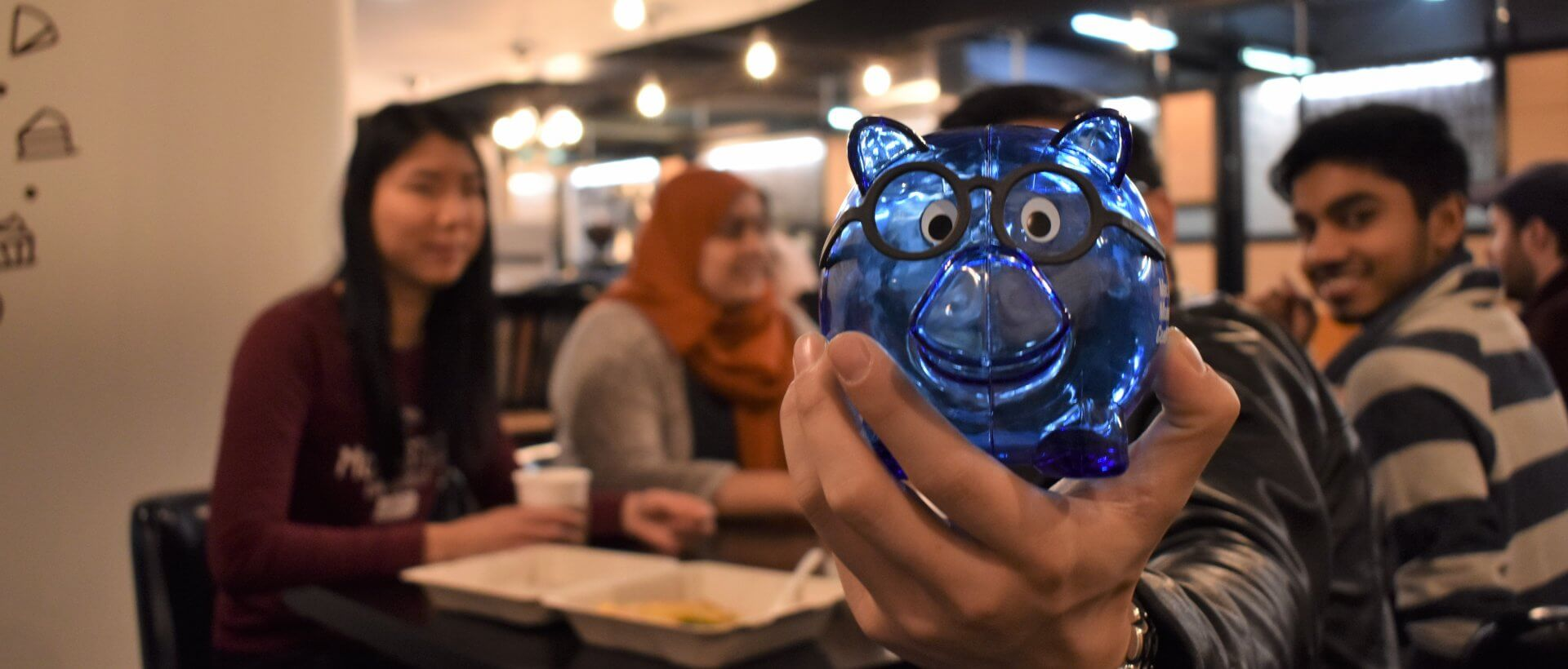 Student holding up a blue plastic piggy bank