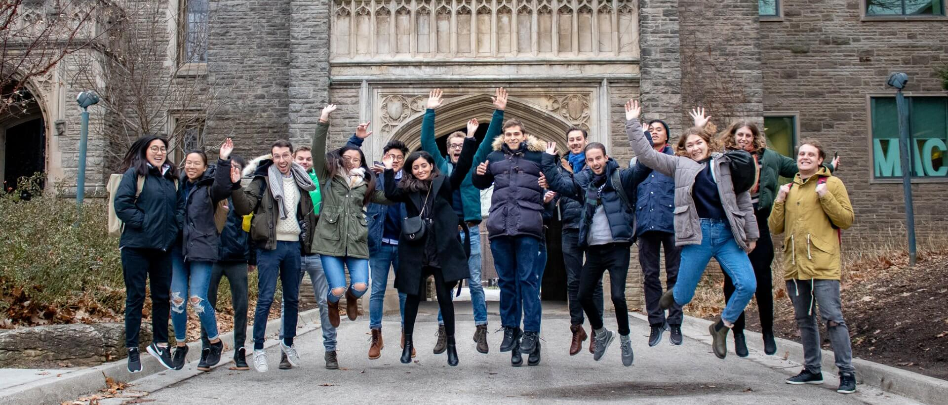 Exchange cohort 2020, group of 16 students jumping in the air outside of University Hall