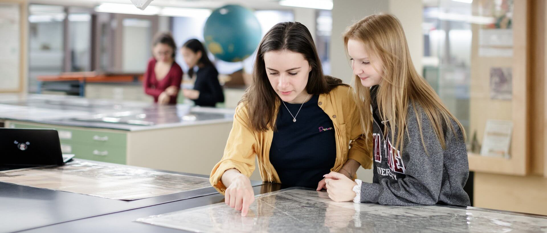 Two students pointing at a map in Mills Library.