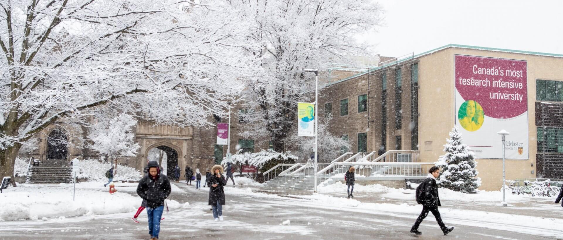 Students walking to class by University Hall, McMaster campus. Winter, snowing.