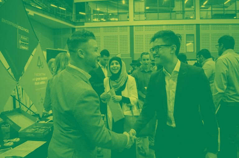 Student and employer shaking hands at Career Fair. Green duo-tone.