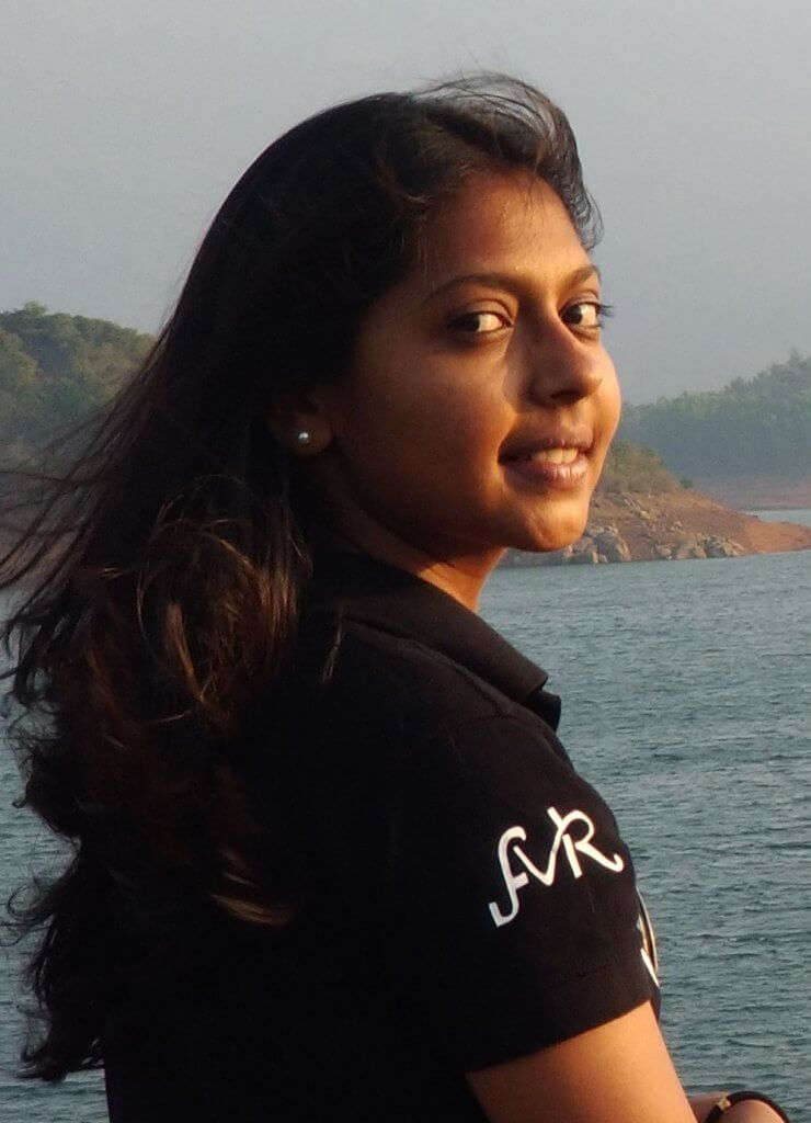 """Student, Vidhya, author of """"The Journey."""" Standing by a body of water."""