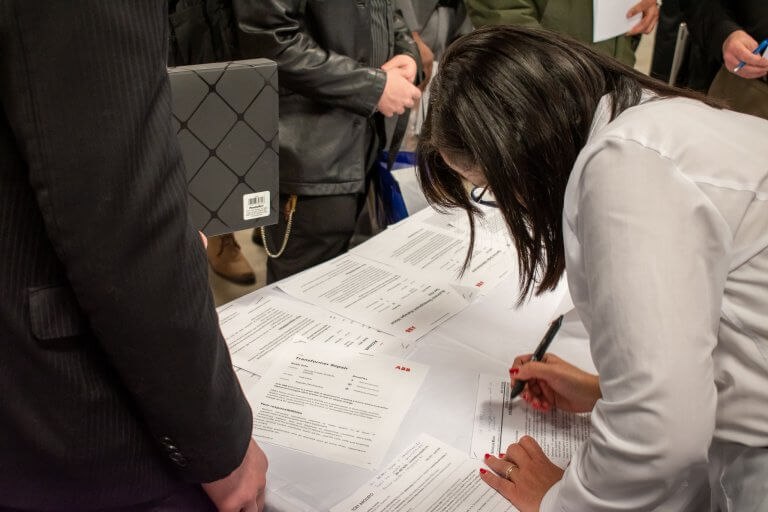 A student writing notes on a job application at Connect to Careers Job Fair. A group of people are standing around the table.