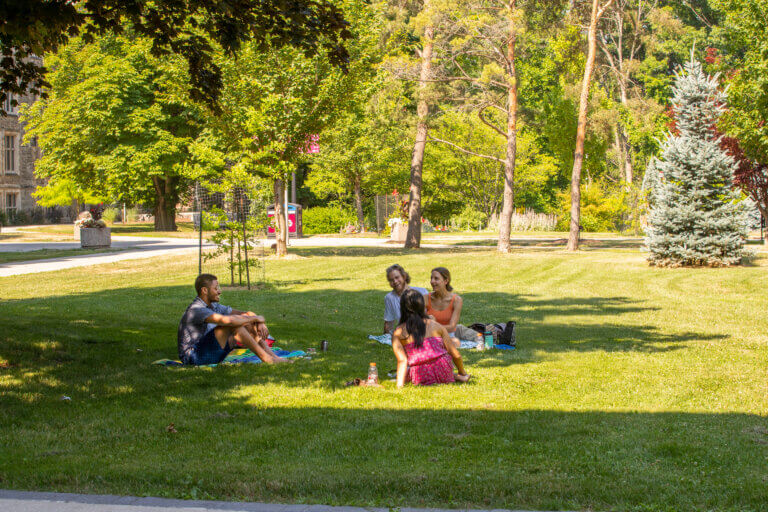 Graduates from Geography and Chemical Engineering sitting on grass outside University Hall. Students practicing social distancing, summer 2020.